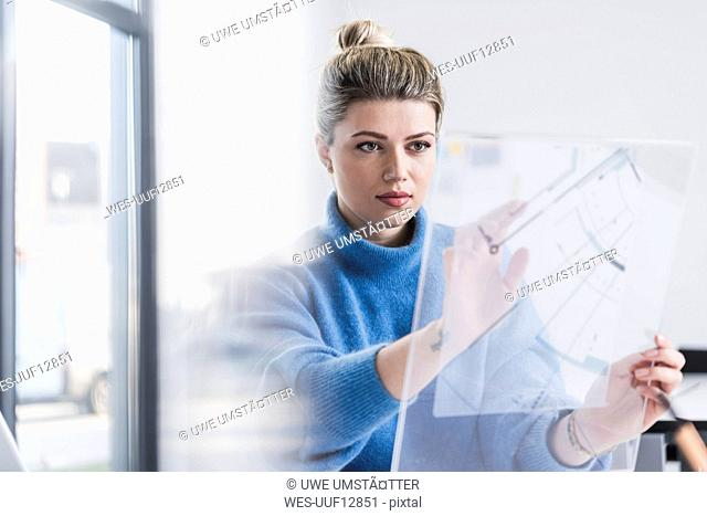 Young woman working on transparent design in office