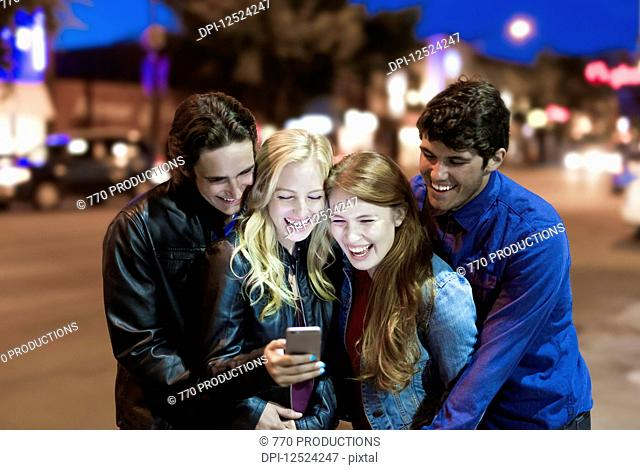 A group of four friends huddle together on a sidewalk looking at a smart phone and laughing as the glow from the screen lights up their faces; Edmonton, Alberta