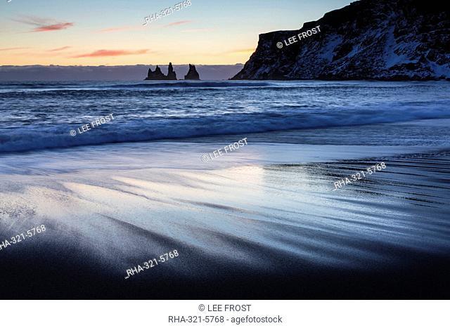 Winter sunset on black volcanic sand beach looking towards rock stacks of Reynisdrangar, Vik, South Iceland, Polar Regions