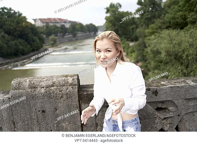 Asian woman on bridge over river Isar in Munich, Germany