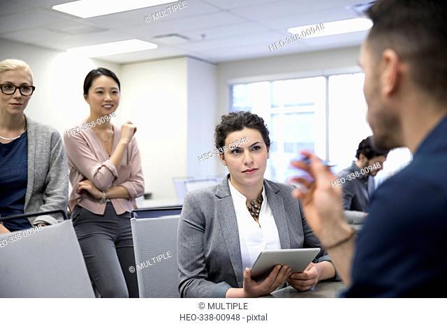 Businesswomen listening to businessman in meeting