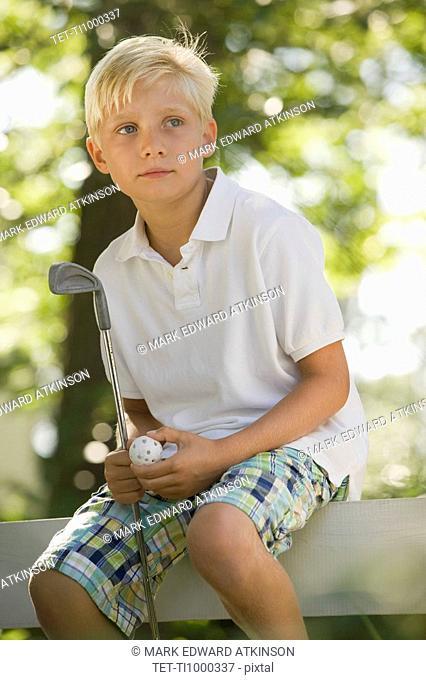 Boy sitting on fence with golf club and ball