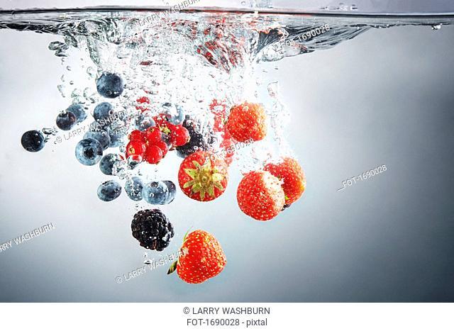 Close-up of various berries in splashing water
