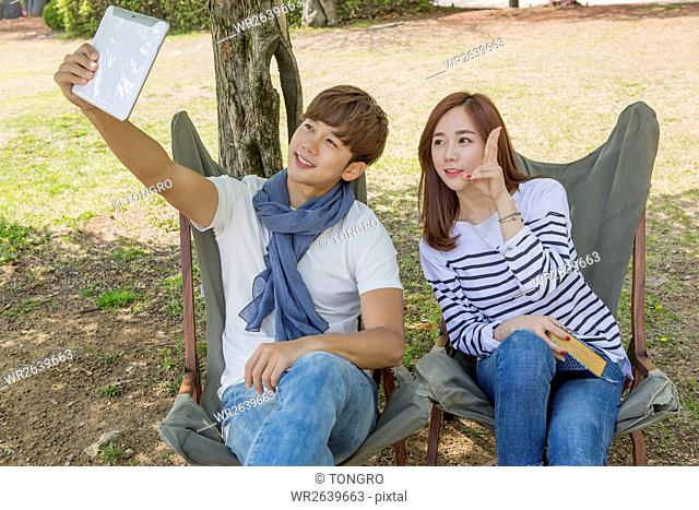 Young smiling couple taking selfie with tablet during date at park in spring