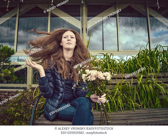 A young red-haired girl corrects her long hair flying from a gust of wind. The girl is sitting on a bench with a bouquet of delicate roses