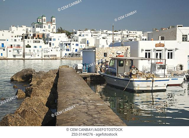 View to the fishing boats and whitewashed houses in Naoussa village with the Church of the Kimisis tis Theotokou at the background, Paros Island