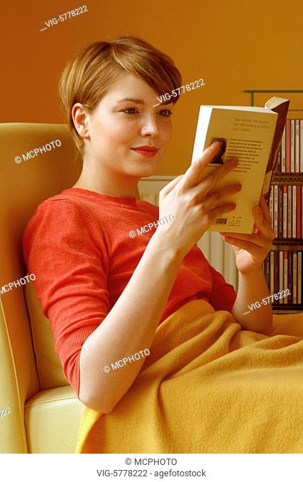 Eine junge Frau liest ein Buch in ihrer Wohnung, 2005 - Germany, 17/07/2005