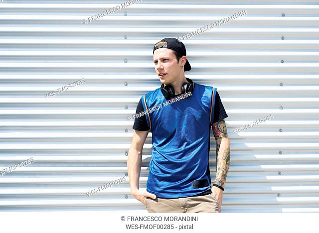 Tattooed young man with headphones and hands in pockets
