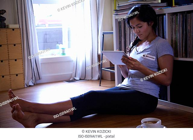 Young woman using digital tablet on floor