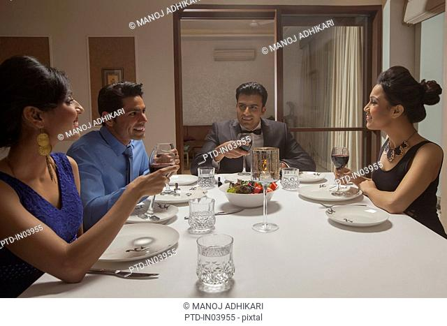India, Friends in formalwear having dinner party