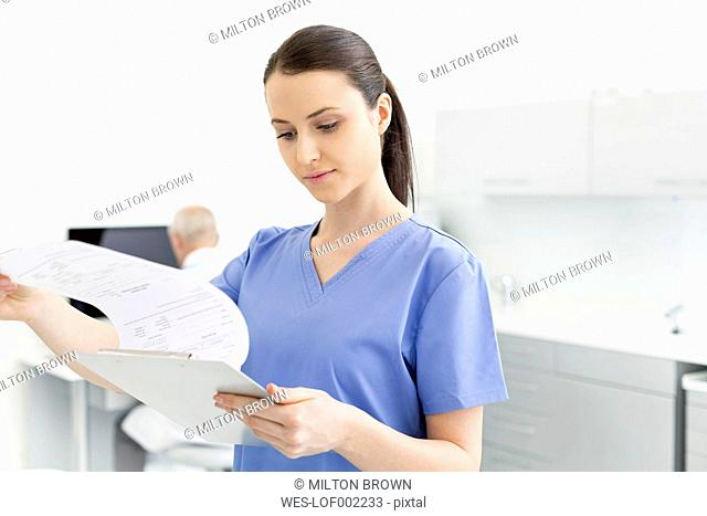 Nurse looking at document with doctor in background