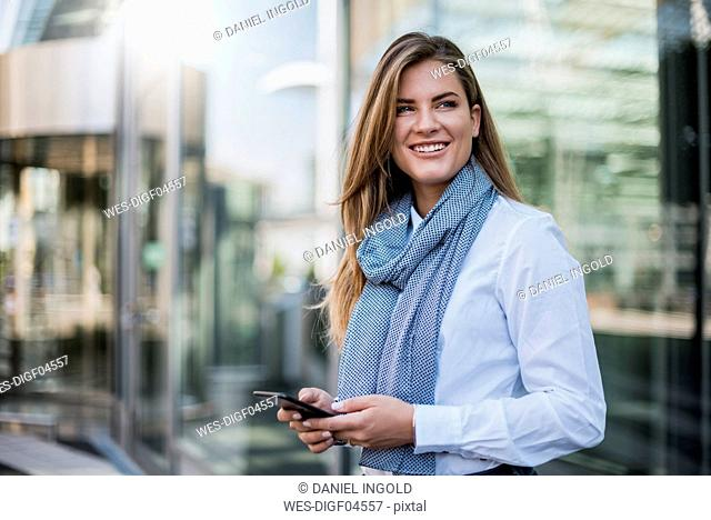 Portrait of smiling young businesswoman with smartphone