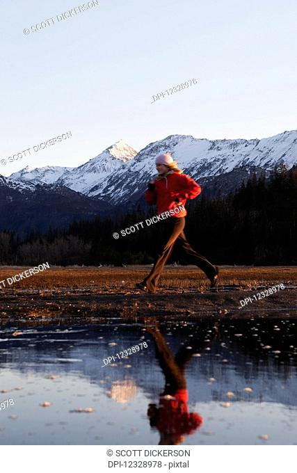 A Young Woman Runs Along The Water's Edge With Her Reflection In The Water And The Kenai Mountains In The Background, Kachemak Bay State Park; Alaska