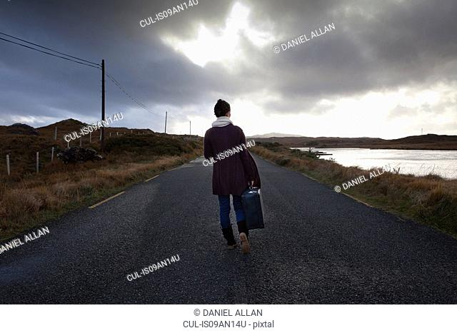 Woman with luggage on road, Connemara, Ireland