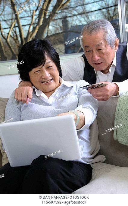 Senior asian couple enjoy time together shopping online