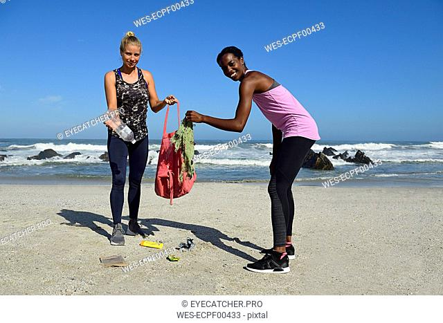 Portrait of two smiling women cleaning the beach from plastic waste