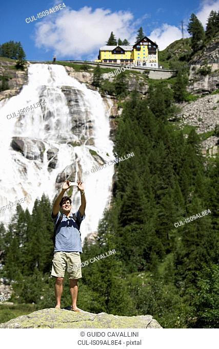 Young man taking smartphone selfie in front of Toce waterfall, Formazza, Verbania, Piemonte, Italy