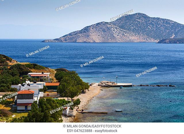 Kamari village and beach on the coast of Fourni island and view of Agios Minas island in the distance, Greece.