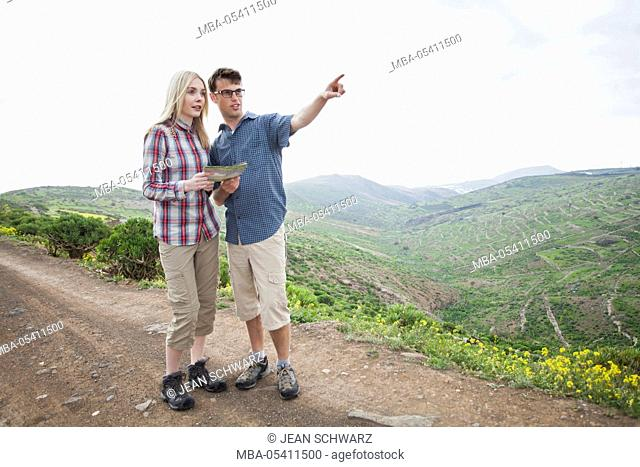 young couple hiking on the Canaries, man showing something to woman in the landscape