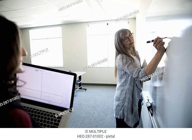 Student watching professor at whiteboard in classroom