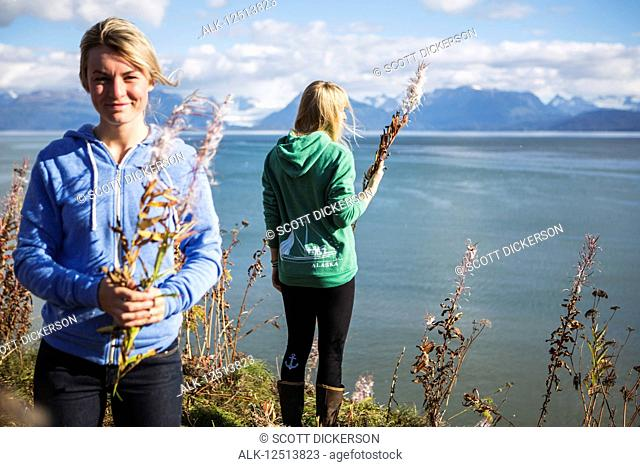 Two women sit on bluff overlooking Kachemak Bay on an autumn day, South-central Alaska; Homer, Alaska, United States of America
