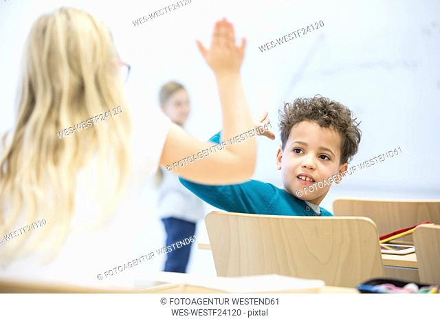 Pupils high fiving in class
