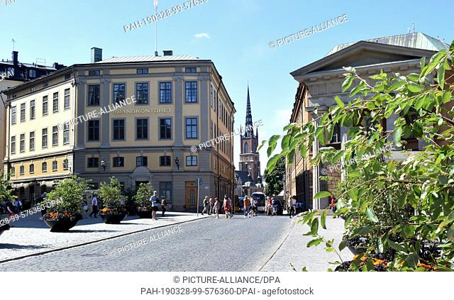 13 July 2018, Sweden, Stockholm: The building with the inscription Brandkontoret (l,Stockholm Fire Insurance Office) and church Riddarholmskyrkan (M