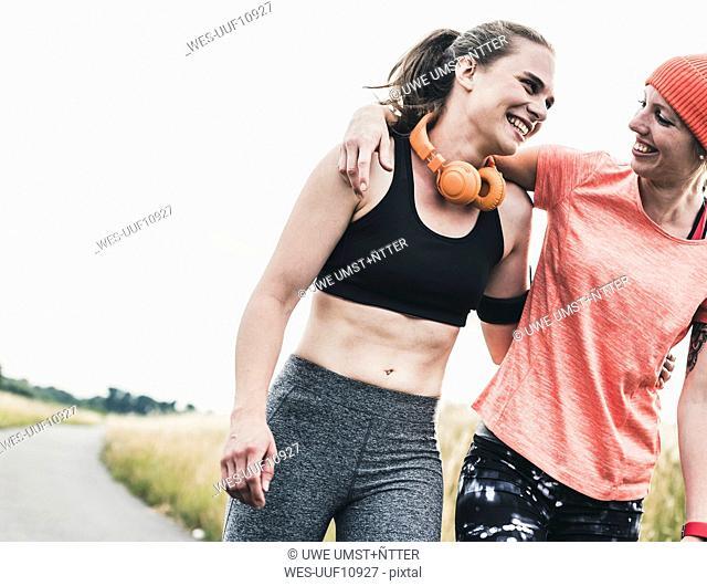 Two happy women having a break from exercising