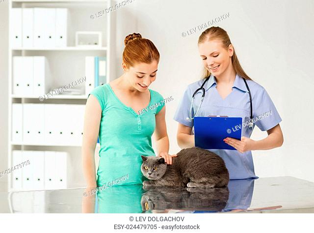 medicine, pet, animals, health care and people concept - happy woman with british cat and veterinarian doctor with clipboard taking notes at vet clinic