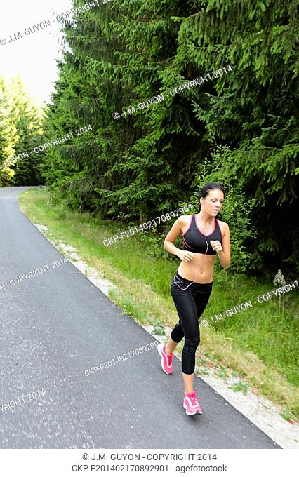 Athlete woman training for marathon run jogging outdoor in countryside