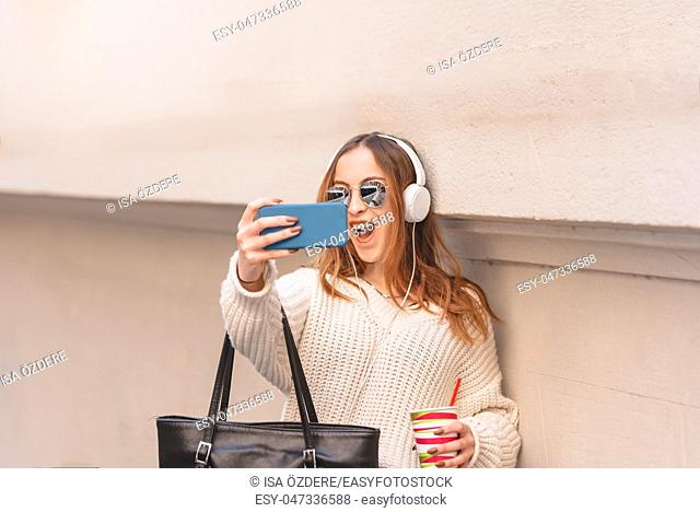 Portrait of beautiful attractive young trendy girl in jumper and jeans with headphones , sunglasses and smart phone takes selfie while leaning on wall