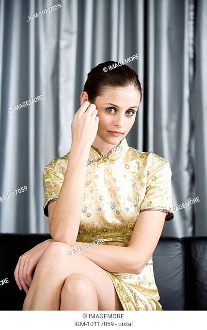 Portrait of young woman in Cheongsam sitting on sofa