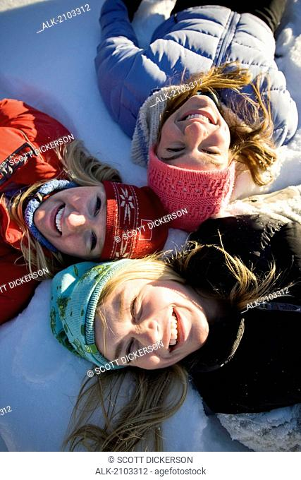 Close Up Of Three Laughing Young Women Laying In Snow Near Homer, Alaska During Winter
