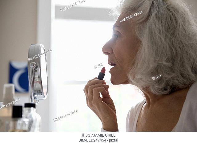 Older woman applying lipstick in mirror