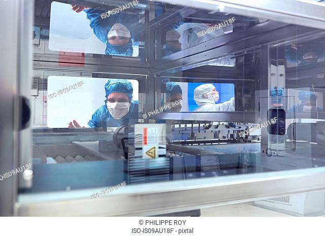 Male worker looking through manufacturing machine window in flexible electronics factory clean room