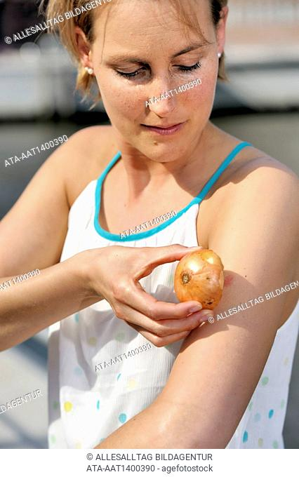 Woman ist treating an insect bite with an onion