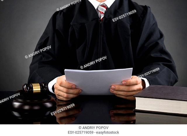 Close-up Of Male Judge Reading Paper In Courthouse