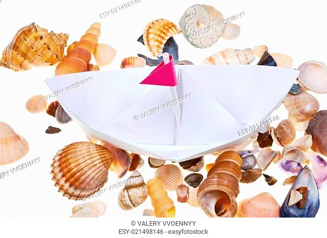 paper boat on background from sea shells