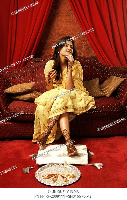 Bride sitting on a couch with henna decoration