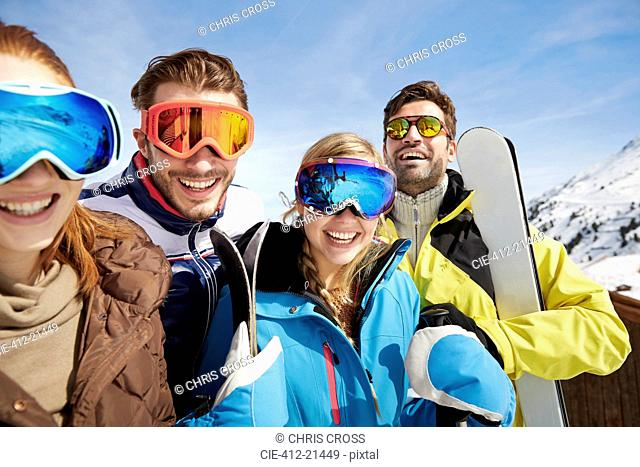 Friends carrying skis on mountain top
