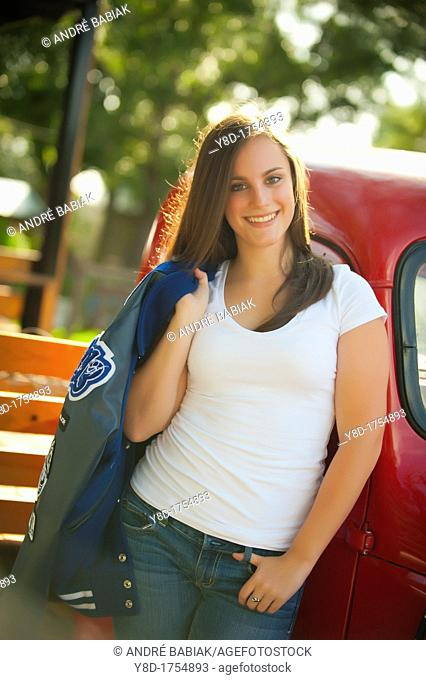 Highschool senior, female caucasian, 17 years old, posing with her school letterman jacket next to vintage automobile