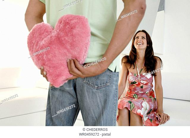 Mid section view of a man hiding a stuffed pink heart behind his back with a young woman sitting on a couch