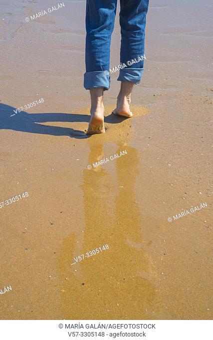 Man's legs walking along wet sand