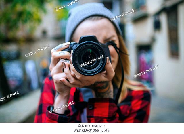 Young woman taking picture of viewer with reflex camera