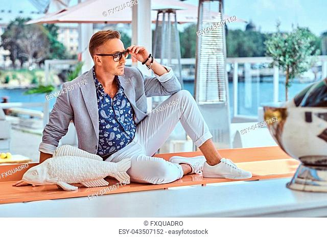 Succesful stylish man dressed in modern elegant clothes sitting on a table with a fish sculpture at outdoor cafe against the background of city wharf