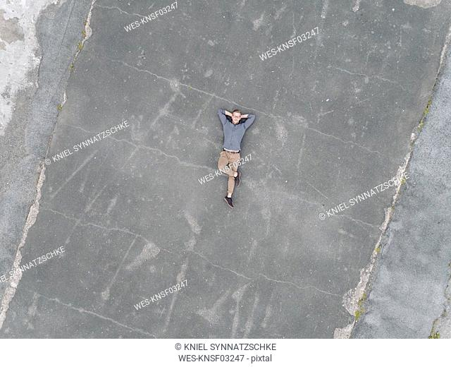 Young businessman relaxing on tarmac, quadcopter viewquadcopter