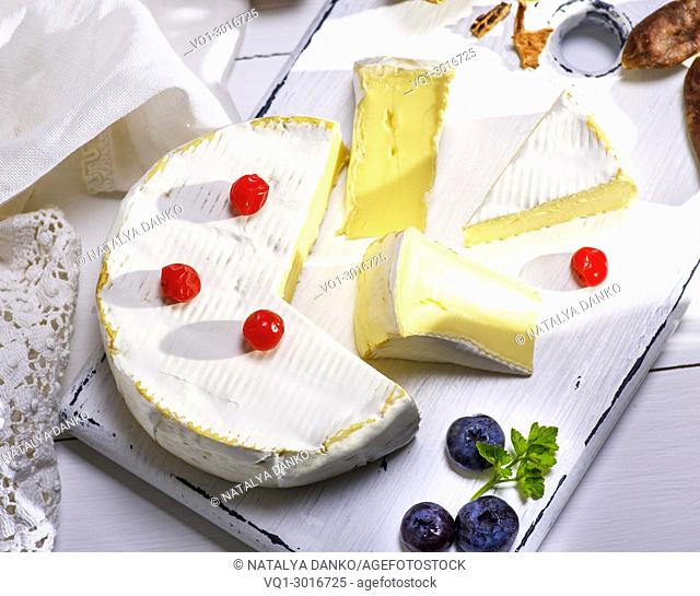 round Camembert cheese sliced on white wooden board, white wooden table, top view
