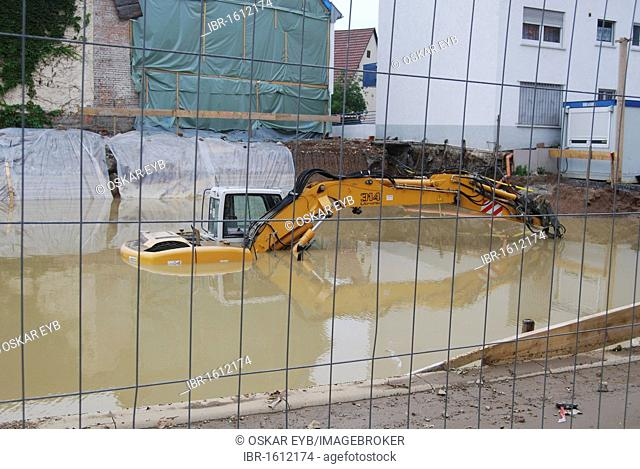 Digger parked in a building pit that is flooded, flooding, high water in Ludwigsburg district, Ditzingen, Baden-Wuerttemberg, Germany, Europe