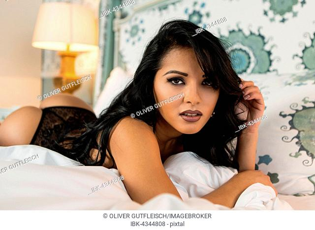 Young woman in lingerie posing on bed, fashion, lifestyle