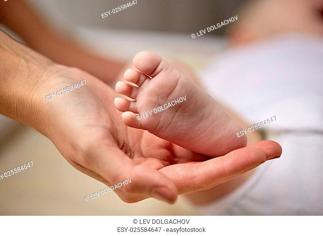 family, motherhood, parenting, people and child care concept - close up of newborn baby foot in mother hand